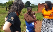 UNFPA Zimbabwe colleagues Rose Katumba and Verena Bruno listen to a pregnant survivor of Cyclone Idai in Chipinge as she narrates how her antenatal care records and medication were swept away by the floods. © UNFPA Zimbabwe